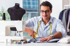 The young man tailor working on new clothing Royalty Free Stock Image