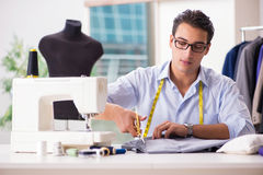 The young man tailor working on new clothing Royalty Free Stock Photo