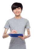 Young man take note on clipboard Stock Photography
