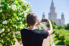 Young man take a photo of high building in big Stock Photography