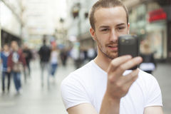 Young Man take picture with cell phone walking Stock Photos