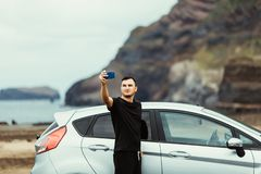 Young man take selfie on the phone near car with ocean view. Car trip. Summer vocation. royalty free stock photo