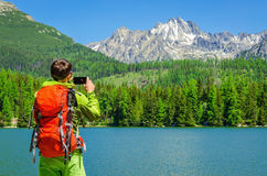 Young man takes a photo of mountain lake, Slovakia Stock Images