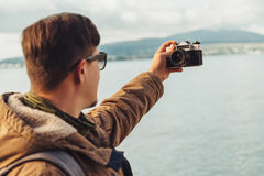 Young man takes photographs self-portrait on coast Royalty Free Stock Photography