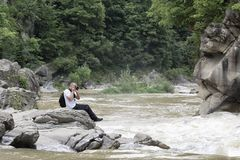 Young man takes pictures on the bank of a stormy river. Sunny su Royalty Free Stock Photography