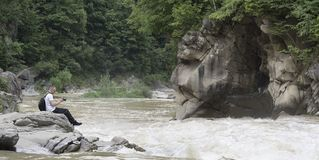 Young man takes pictures on the bank of a stormy river. Sunny su Royalty Free Stock Photo