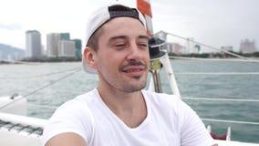 Man takes self portrait photo while enjoying vacation on a yacht. Young man takes self portrait photo while enjoying vacation on a yacht stock video footage