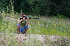 Young man taking aim with the air rifle Stock Images