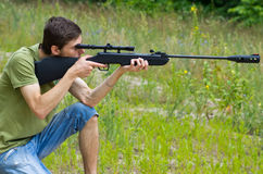 Young man taking aim with the air rifle royalty free stock image