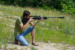 Young man taking aim with the air rifle stock photo