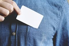 Young man is taking a blank card in the pocket of his shirt. stock photo