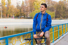 Young Man Taking a Break on Bicycle in Park Stock Photography