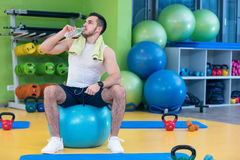 A young man taking a break at the gym sitting on a pilates ball with a bottle of water Stock Photography
