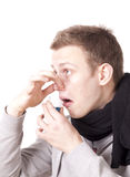 Young man taking cough syrup. Young man with scarf feeling sick, making a disgusted face while taking cough syrup Royalty Free Stock Photography