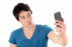 Young man taking a kissing selfie photo with his smart phone. Stock Photos