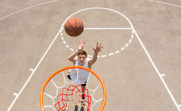 Young Man Taking Lay Up Shot on Basketball Court Royalty Free Stock Image