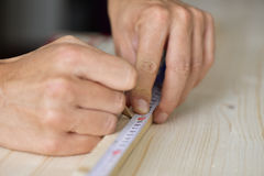Young man taking measurements in a wooden board Stock Image