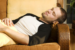 Young man taking a nap on couch. In living room Royalty Free Stock Images