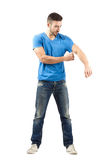 Young man taking off his shirt while holding sleeve Royalty Free Stock Photography