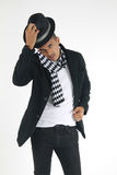 Young man taking off his top hat. Mixed race male standing up taking off his top hat who is wearing a checkered scarf staring at a subject Royalty Free Stock Photos