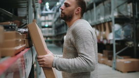 Young man taking a pasteboard box from a shelf, holds in hands item in a warehouse. 4K. Young man with beard taking a pasteboard box from a shelf. Holds in hands stock footage