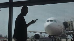 Young man is taking photo from airport building window. stock footage