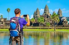 Young man taking photo of Angkor Wat, Cambodia. Young man is taking a photo of Angkor Wat temple, Siem Reap, Cambodia Royalty Free Stock Image