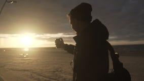 Young man taking photo at the beach. 25.03.2017 - JURMALA - LATVIA stock video footage