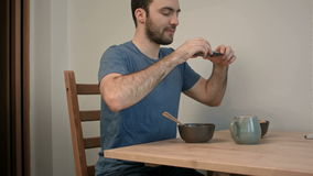 Young man taking photo of breakfast using smartphone. Professional shot on BMCC RAW with high dynamic range. You can use it e.g. in your commercial video stock video footage