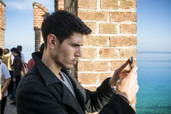 Young man taking photo with cell phone of the Stock Image