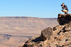 Young man taking photo on the edge of the canyon Stock Photo