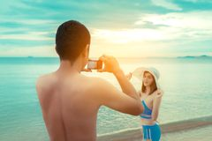 Young man taking photo girlfriend bikini royalty free stock images