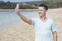 Young man taking photo of himself using mobilephone camera Royalty Free Stock Photo