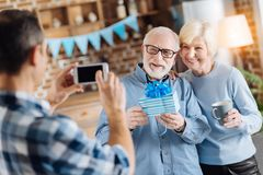 Young man taking photo of his elderly parents holding gift. Happy moments of life. Loving young son taking a picture of his elderly parents posing with a royalty free stock images