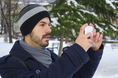 Young man taking a photo with his smartphone. In winter Stock Photo