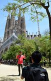 Young man taking photo of mature person with La Sagrada Familia in the background royalty free stock photography