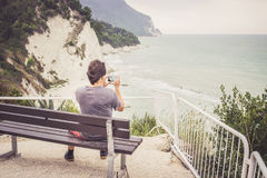 Young man taking photo of sea landscape on his cellphone Royalty Free Stock Image