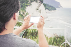 Young man taking photo of sea landscape on his cellphone. Young man holding smart phone with white empty screen in Numana, Marche, Italy. Travel concept royalty free stock photo