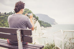 Young man taking photo of sea landscape on his cellphone. Young man using smart phone for taking photo of seaside panorama in Numana, Marche, Italy. Travel royalty free stock photography