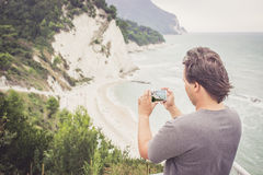 Young man taking photo of sea landscape on his cellphone. Young man using smart phone for taking photo of seaside panorama in Numana, Marche, Italy. Travel stock image