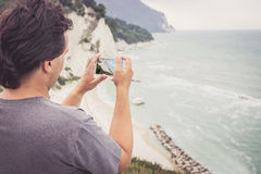 Young man taking photo of sea landscape on his cellphone. Young man using smart phone for taking photo of seaside panorama in Numana, Marche, Italy. Travel stock photography