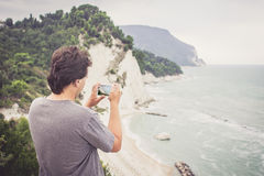 Young man taking photo of sea landscape on his cellphone royalty free stock images