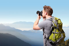 Young man taking photo on top of mountain Stock Photo