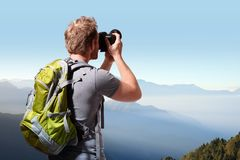 Young man taking photo on top of mountain Stock Images
