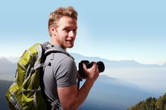 Young man taking photo on top of mountain Royalty Free Stock Photo