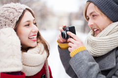 Young man taking photo of woman in winter Royalty Free Stock Image