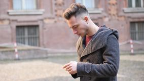 Young man taking photograph with smartphone outdoor. Young man taking photograph or filming video of historic place in European city with smartphone in a winter stock video