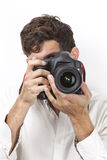 Young man taking photograph with vintage camera against white background Stock Photo