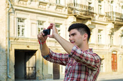Young man taking photographs. Young man standing taking photographs with a compact camera outside an old historical building Stock Images
