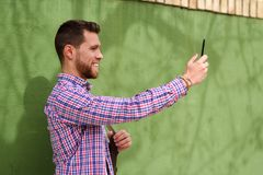 Young man taking photographs with his smart phone in urban backg Royalty Free Stock Photography